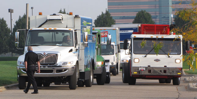 A parade of about 40 hybrid- and electric-drive trucks enters a parking lot at the Hyatt Regency Dearborn to start a ride-and-drive function at the Hybrid Truck Users Forum. (Photo by Tom Berg)