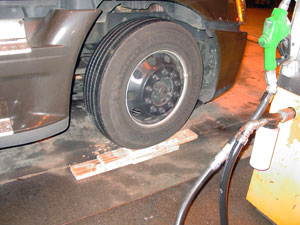 Type IV procedures are exacting, and include the need to level the truck during fueling, done here by driving a steer-axle wheel onto lumber.