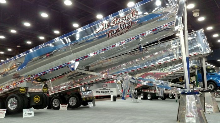 New Mac aluminum end-dumps gleam in the lights of the Mid-America