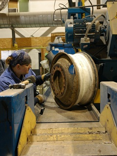 An operator visually inspects a wheel prior to the blast cleaning process.