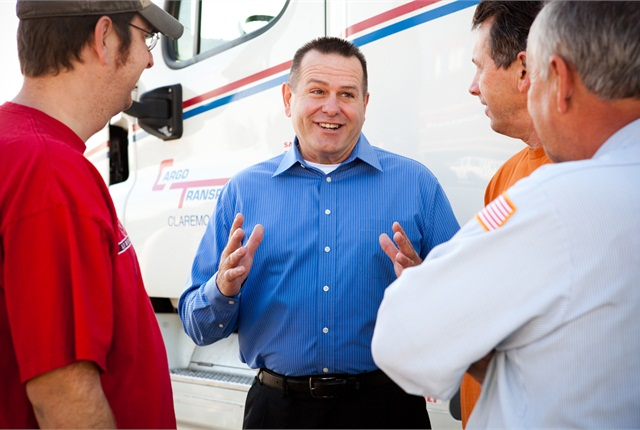 Dennis Dellinger,president of Cargo Transporters, with some of the company's drivers. The company makes use of its mobile communications and telematics technologies to improve mpg and reduce paper.