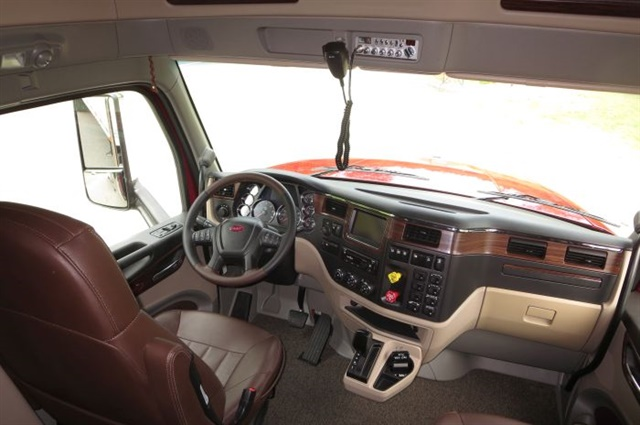 Simulated dark wood trim graces the dashboard and door panels, while dark brown leather covers the seats. Of course it has power windows and locks.