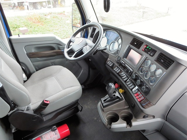 Dump truck's comfortable interior includes contoured driver's set and premium touches among gauges and controls. Red switches at lower right operate the Rogue dump bed.