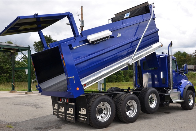 This 18-foot steel dump body has a combination double-acting and high-lift tailgate that works well with loads like large rocks, and a forklift can push palletized cargo aboard. The gate is operated by a pair of air cylinders, one on each side, so the driver can stay in the cab.