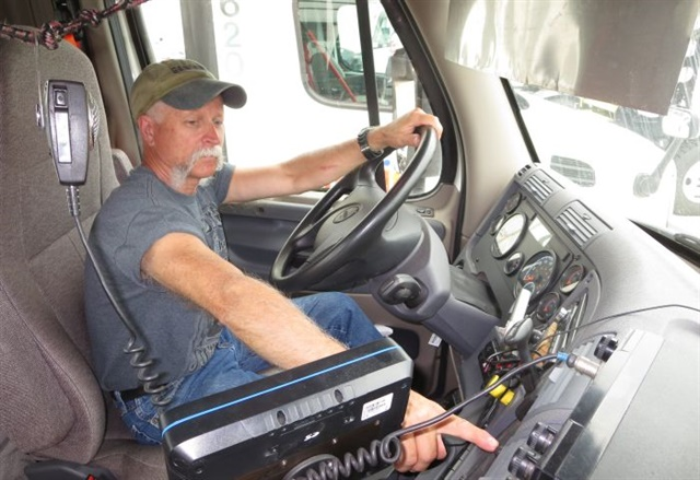 Meijer Logistics driver Ron Diamond points to the button that can save him considerable work and time — and prevent an injury — during a hookup.