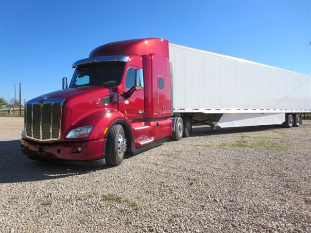 The metallic red 579 is Peterbilt's main aerodynamic highway model. The compact 56-inch mid-roof sleeper weighs several hundred pounds less than long-and-tall boxes, but has decent interior room with well-thought-out storage places.