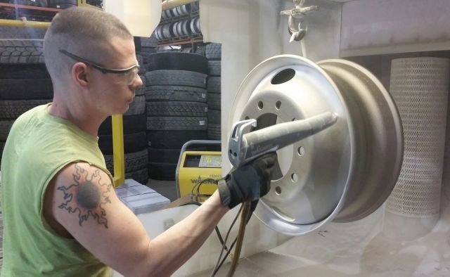 """Juan Klinehoffer, the """"wheel man"""" at Bob Sumerel Tire in Zanesville, Ohio, air-sprays positively charged powder at the negatively charged wheel. There it clings until curing."""