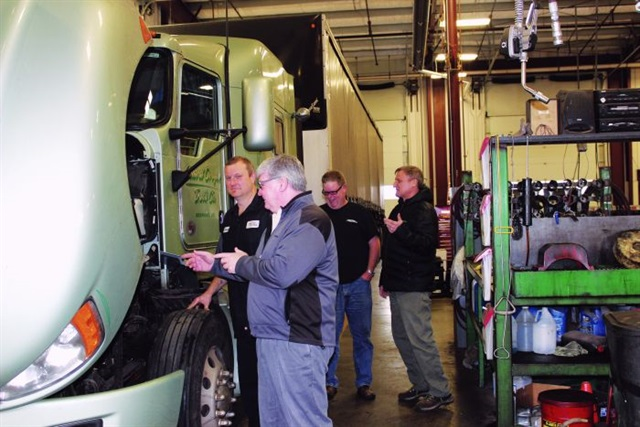 Central Oregon Trucking Co.'s Phil Taylor (foreground) checks in with a mechanic handling a PM inspection. Photo: courtesy Central Oregon Trucking Co.