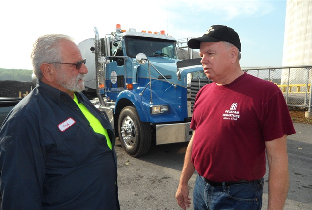 Veteran Driver Jack Mirando (left) and Fleet Supervisor Larry Fingar discuss the Kenworth-Etnyre rig and its planned run to a Peckham asphalt plant about 110 miles north.