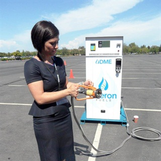Rebecca Boudreaux, president of Oberon Fuels, shows a 21-gallon-per-minute dispenser that priced at $21,000. Nozzle twists onto a vehicle's filler neck. Propane-type storage tank costs $1 to $3 per gallon.