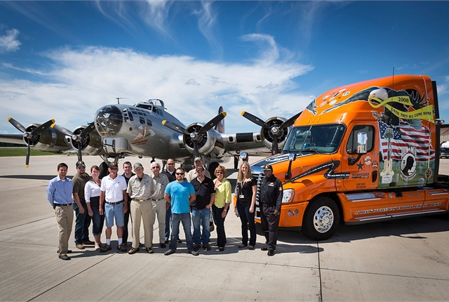 "Schneider National recently sponsored a stop in Green Bay, Wis., for theExperimental Aircraft Association's World War II-era B-17 ""Aluminum Overcast."" A few Schneider employee-vets and their spouses rode over the area in the bomber, then posed with it and one of the carrier's specially decorated Ride of Pride tractors at the airport."