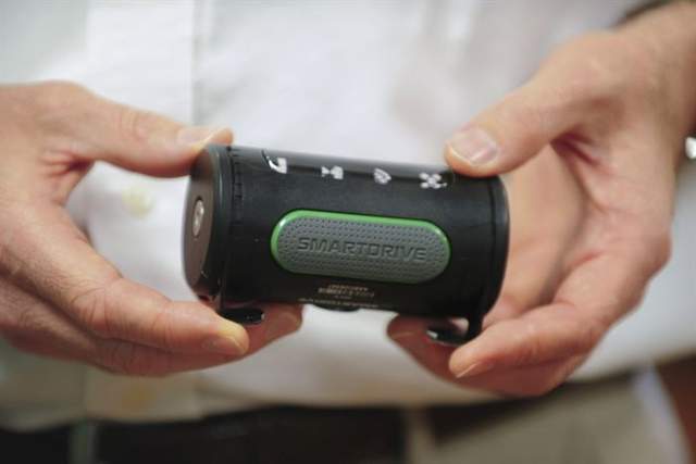 The SmartDrive camera is a small black cylinder with a camera on one side and a button on the other.