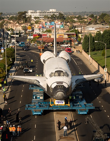 A typical scene as the Endeavour travels through residential neighborhoods and business districts along the transport route. Note in the photo on the left that the SPMT setup has been altered to a wide stance to span over the median.
