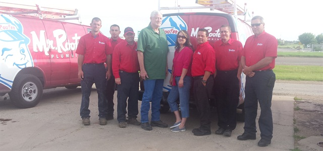 Brandy Waugh and her father (center) pose with the company's team of technicians and cargo vans.