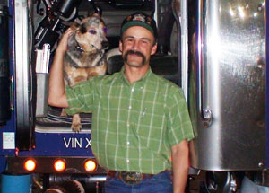 Miles Verhoef, pictured with his dog Trixie, keeps cost down by eating in his truck and using an APU to limit idling.
