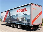 High-cube Kögel Mega van has the usual rear doors plus curtain sides and a liftable roof tarp, allowing loading and unloading from docks and over its sides and top. Photo: Kögel