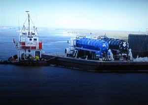 Tanker trucks are shown on a barge in this TV ad from BP about their cleanup efforts.