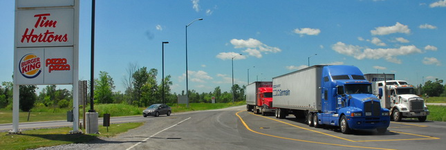 Tractor-trailers parked in a designated LCV Only parking area on Ontario's Hwy 401 near Kingston, Ont.