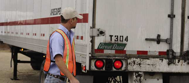 A fleetHQ technician inspects a trailer where it's parked, and after a go-ahead from Paschall Truck Lines, will fix whatever's wrong.