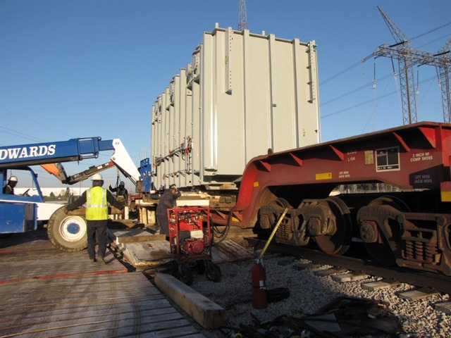 Crew uses extended-boom forklift to place rails under the load on the