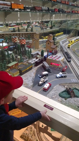 Little boy enjoys the street scene on an S-guage layout. But, how d