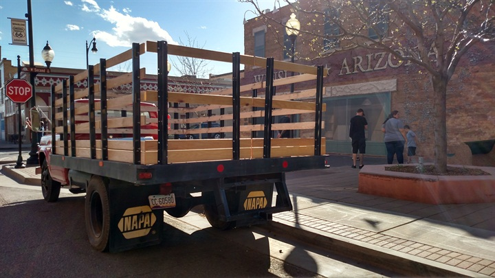 Steel flatbed body wears tall stakes with wooden slats. Imagine what