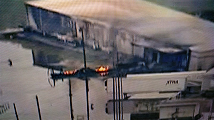 Aerial video shows what appear to be remains of a smouldering trailer.