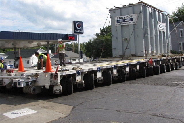 "First nine ""lines"" of wheels are hydraulically steered left and the last nine are steered right as the trailer makes a sharp left turn onto a parking lot."