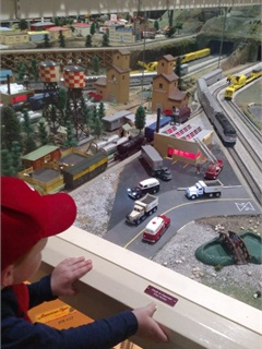 Little boy enjoys the street scene on an S-guage layout. But, how'd those trucks get over the rail crossing?