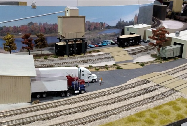 At a flooring mill, three rigs are backed against the dock while their drivers shoot the bull as they wait to load. Hopper cars (at top) will carry away sawdust.