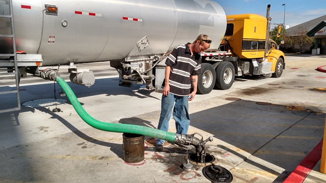 Driver Jeff McMannus checks progress as he delivers a load of biofuel through an appropriately green hose. He was careful to avoid spills. Photos: Tom Berg