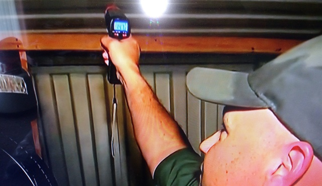 Border Patrol agent uses a laser thermometer to read the temperature near the trailer's ceiling. It registered 143.6 degrees Fahrenheit.