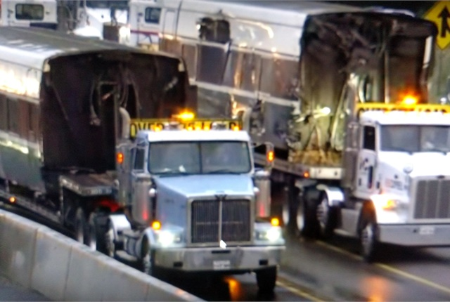 Passenger cars were loaded aboard standard flatbed, drop-deck and lowboy trailers for movement from the scene. Screen capture from YouTube.com, Puget Sound Rail Productions.