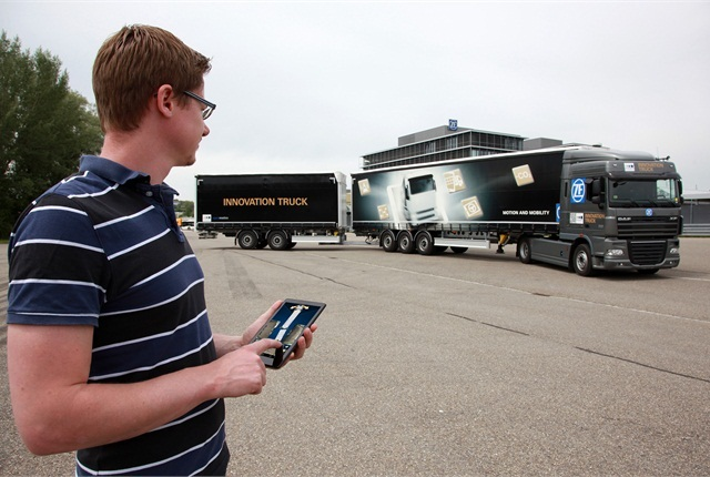 The tractor's steering and movement are remotely controlled by a man with special app on a tablet computer. It sends the pup trailer in the proper path, and the semitrailer and tractor follow along, guided by the ZF app's computation. Photo courtesy ZF.