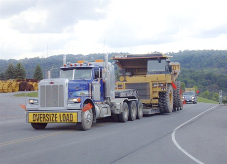 Peterbilt 388 tractor, assembled from a glider kit, has a lift axle ahead of its tandem and a 600-hp Cat C16.