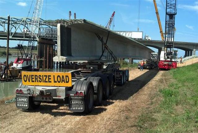 "Rear of load is supported by a ""steer car"" and ""jeep"" owned by V. Van Dyke, Inc., of Seattle, which hauled eight beams from Tacoma. WashDOT photo."