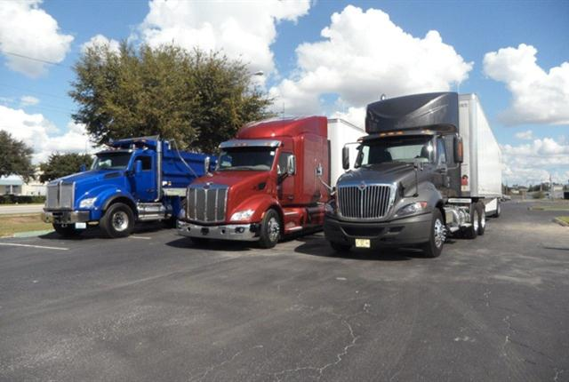 Three heavy duty entries rest at day's end. From left, Kenworth T880 dump, Peterbilt 579 sleeper-cab tractor and International ProStar+ daycab tractor.