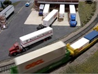 Container train rolls by as tractor-trailers come and go. Is the