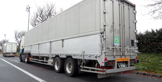 Like all commercial vehicles of any size, this trailer sports underride barriers on three sides. Its tractor's engine was idling, like all other heavy vehicles at this Japanese truck stop.