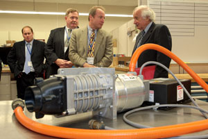Eaton's Vice President and General Manager, Hybrid Power Systems, Dimitri Kazarinoff, center, updates U.S. Representative Sander Levin, right, on company commercial truck hybrid technology during a tour of the Eaton Innovation Center.