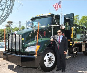Keith Kerman, assistant commissioner for the New York City Parks Department, is shown with one of the department's 17 Kenworth T370 diesel-electric hybrid trucks.