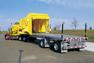 Roll-Tite offers retractable tarpaulin systems for specialty trucks, drop decks, straight trucks, and flat beds, such as this one.