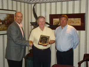 Greg Smith (left), vice president of sales and marketing for Talbert, and Russ Losh (right), Northeast area sales manager for Talbert, present the award to Barry Hale (center), president of Hale Trailer.