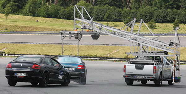 Courting danger: On a Bosch test track, the black demo car approaches the dummy car too quickly, alerting the radar system, which applies the brakes in time to prevent or at least soften the crash. Photo: Bosch.