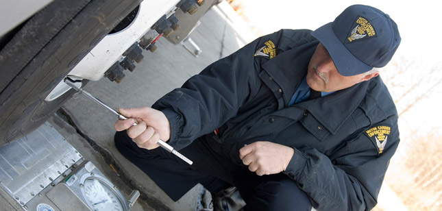 A motor carrier enforcement officer from Ohio inspects a truck's tires. (Photo courtesy of the Ohio State Highway Patrol)