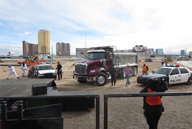Play-acting cops have cornered a new International HX620 dump truck and collared three crooks, amusing an audience of dealers, customers and reporters. But they heard that Navistar's serious about the vocational business. Photo: Tom Berg