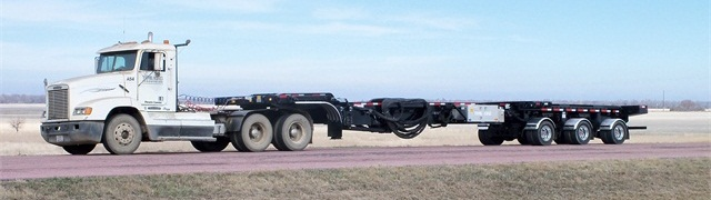 Blade hauler contracts to 53-foot length for empty travel.