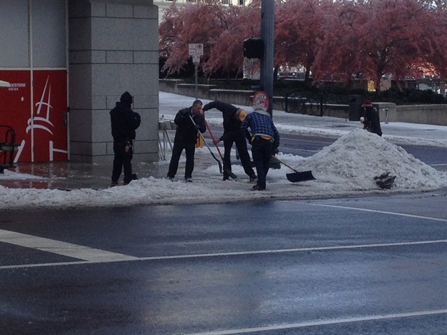 City crews work to clear ice from sidewalks, which make for hazardous conditions for pedestrians. Photo by Jim Park