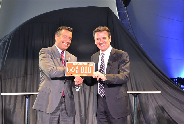 Nevada Gov. Bob Sandoval, left, and Daimler's Wolfgang Bernhard, right, show off the first autonomous truck license plate in the U.S. Photo: Stephane Babcock