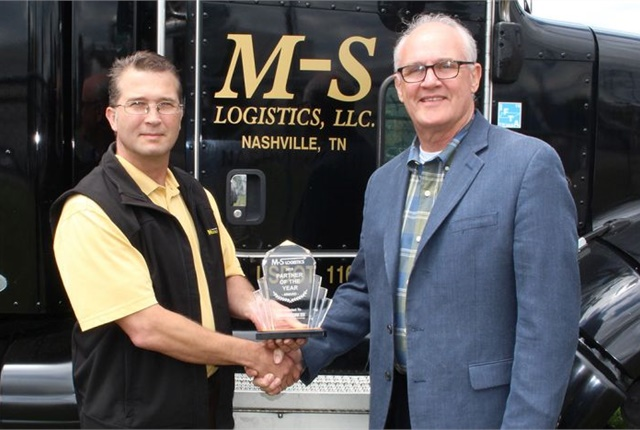 Mike Elliott of M-S Logistics (left) hands the Partner of the Year Award to Bill Sweatman, president of Marangoni Tread N.A. Photo: Marangoni Tread N.A.